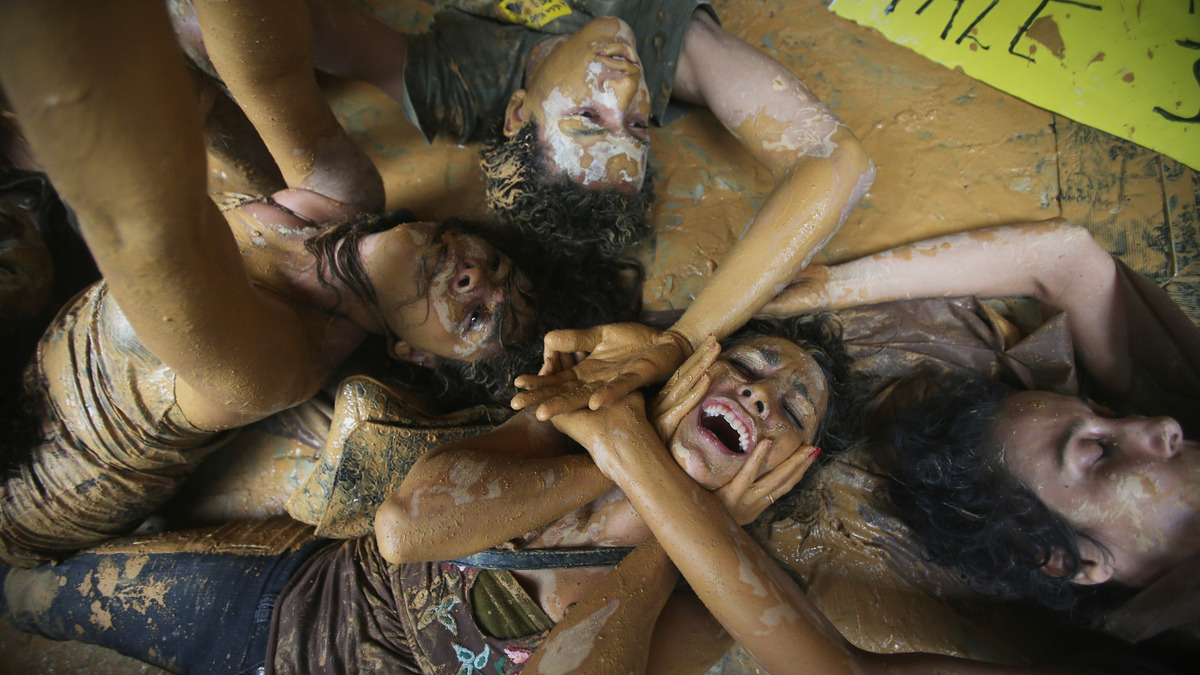 RIO DE JANEIRO, BRAZIL - NOVEMBER 16: Protestors perform lying in muddy water which they spashed at the entrance to Vale headquarters on November 16, 2015 in Rio de Janeiro, Brazil. The bursting of two dams at the Samarco mining operation, jointly owned by Vale and BHP Billiton, unleashed a flood of muddy waste which mostly levelled a village in Minas Gerais state. The massive mudflow left ten people dead and an environmental aftermath polluting downstream waters. (Photo by Mario Tama/Getty Images)